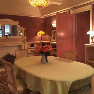 Dining room modeled after Mark Twain's library with rose walls, low bookcases, Tiffany lamp and overhead light