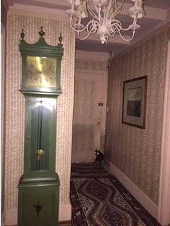 Wallpapered hallway with grandfather clock, crystal chandelier and turkish carpet