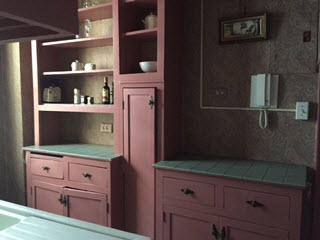 Dark rose painted cabinets and open shelves, green ceramic tile counters, pale paisley wallpaper in the kitchen